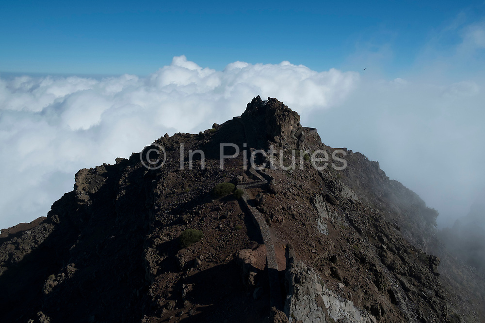 View from the Roque de los Muchachos looking south to the Caldera de Taburiente National Park in La Palma, Canary Islands, Spain. La Palma, also San Miguel de La Palma, is the most north-westerly Canary Island in Spain. La Palma has an area of 706 km2 making it the fifth largest of the seven main Canary Islands. Caldera de Taburiente National Park Spanish: Parque Nacional de la Caldera de Taburiente is a national park on the island of La Palma, Canary Islands, Spain. It contains the enormous expanse of the Caldera de Taburiente, once believed to be a huge crater, but nowadays known to be a mountain arch with a curious crater shape, which dominates the northern part of the island. It was designated as a national park in 1954. The caldera is about 10 km across, and in places the walls tower 2000 m over the caldera floor.