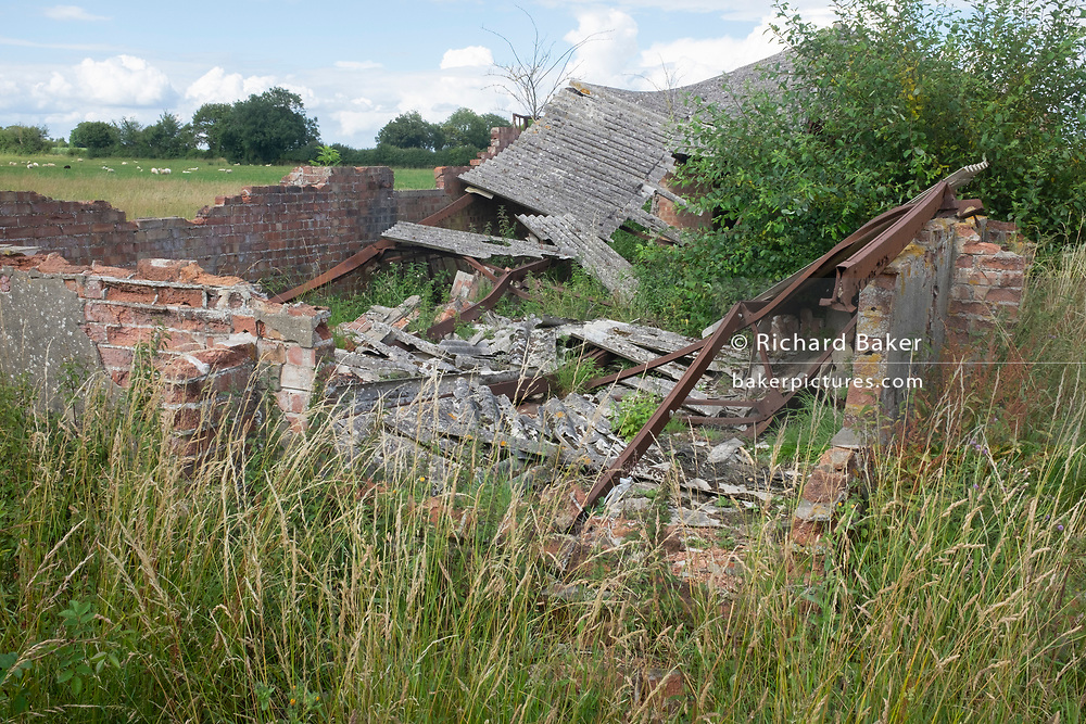 A derelict building now used for agricultural purposes but once part of the WW2-era RAF Lavenham,  a former bomber base used by the United States Air Force in the 1940s, on 10th July 2020, in Alpeton, Suffolk, England. Lavenham airfield was built during 1943. The technical site and administrative buildings were on the southern side of the airfield as were most of the dispersed temporary buildings which gave accommodation for 2,900 personnel.