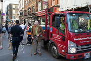Elderly man seems bemused by all that is going on around him as work trucks arrive working on the redevelopment, many would say gentrification of Soho, London, England, United Kingdom.