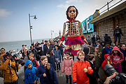 Little Amal took her first steps in the United Kingdom today when she arrived to a warm welcome from local school children and Actor Jude Law in Folkestone, United Kingdom on the 19th of October 2021.  Little Amal is a 3.5 metre-tall living artwork of a young Syrian refugee child who has spent the last 3 months walking 8000 km from the boarder of Syria across Turkey, Greece, Italy, France, Switzerland, Germany, Belgium to the UK to focus attention on the urgent needs of young refugees.