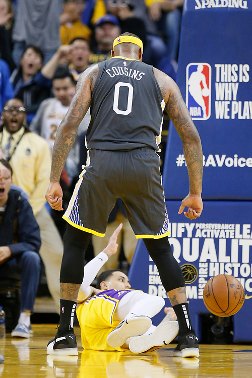 Golden State Warriors center DeMarcus Cousins (0) dunks on Los Angeles Lakers forward Kyle Kuzma (0) in the second half of an NBA game at Oracle Arena on Saturday, Feb. 2, 2019, in Oakland, Calif. The Warriors won 115-101.