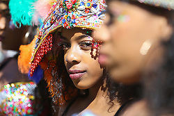 © Licensed to London News Pictures. 29/08/2016. Leeds, UK. A costumed woman looks towards the camera during the Leeds West Indian Carnival in Leeds, West Yorkshire. First run in the 1960's, the Leeds West Indian Carnival is Europe's longest running authentic Caribbean carnival parade. Photo credit : Ian Hinchliffe/LNP