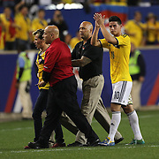 A fan runs onto the pitch to ask James Rodriguez, Colombia, for his autograph while being substituted during the Colombia Vs Canada friendly international football match at Red Bull Arena, Harrison, New Jersey. USA. 14th October 2014. Photo Tim Clayton