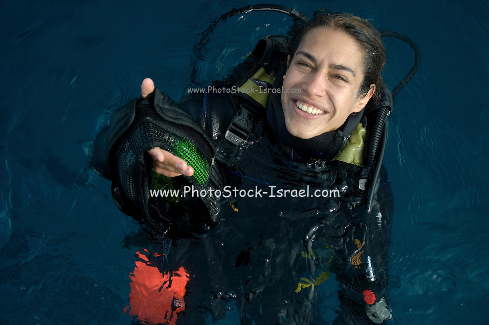 Female diver coming out of the water at the end of a dive handing her weight belt to the people on the pick up boat.