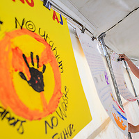 071815       Cable Hoover<br /> <br /> Teracita Keyanna hangs posters that walkers carried in the annual Churchrock Uranium Tailings Spill Memmorial Saturday in the Red Water Pond community.