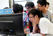 Teenagers surround a computer screen at the ChinaJoy Expo, also know as the China Digital Entertainment Expo and Conference,  in Shanghai, China on 29 July, 2011. Online and social network games have become hugely popular in China as Chinese children lack the space and facility require for sports, spurning worries from parents and government officials on internet addiction.