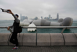 March 26, 2019 - Hong Kong, China - A visitor takes a photo of himself with the KAWS:HOLIDAY installation on display in Hong Kong's Victoria Harbor. The KAWS:Holiday enlarged structure by American artist Brian Donnelly, also known as KAWS, will be on display until March 31, 2019. (Credit Image: © Christopher Jue/ZUMA Wire)