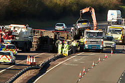 © Licensed to London News Pictures.  23/11/2012. BANBURY, UK. Police and highway agency workers attempt to recover a car transporter that has overturned between J12 and J11 on the M40 motorway near Gayford. The motorway was closed in both directions for a time resulting in long delays. Photo credit :  Cliff Hide/LNP