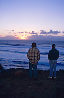 Two men watch the sunset over The Pacific Coast from Sea Ranch, California.