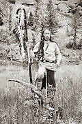 Cherokee Native American Indian in traditional costume against rock cliffs in western Wyoming.