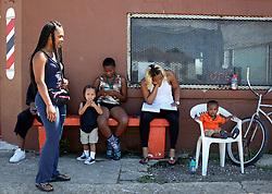 26 August 2015. New Orleans, Louisiana. <br /> Hurricane Katrina revisited. <br /> Rebuilding the Lower 9th Ward. <br /> People hang outside Galvez Goodies Grocery store and barber shop. Galvez is the only grocery store in the area classified as a 'food desert.' <br /> Photo credit©; Charlie Varley/varleypix.com.