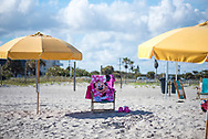 Cocoa Beach, Florida, USA - December 13, 2020: A beach towel featuring the Disney character Minnie Mouse is draped over a chair at the beach in Cocoa Beach, Florida