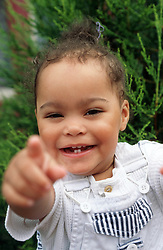 Portrait of young girl pointing and smiling,