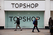 People walk past the shop front to high street fashion chain store, Topshop. London.