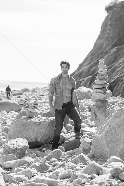 man with open shirt on a rocky beach