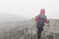 Female hiker decends rocky mountain ridge in thick clouds