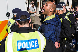London, UK. 10th June, 2018. A man from a far-right group sticks out his tongue as police officers detain him before the pro-Palestinian Al Quds Day march through central London organised by the Islamic Human Rights Commission. An international event, it began in Iran in 1979. Quds is the Arabic name for Jerusalem.