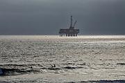 Oil Derrick and surfers off coast of Huntington Beach, Orange County, California, USA
