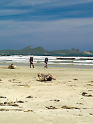 View of the beach at Mason Bay, Stewart Island (Rakiura), New Zealand, with two trampers on the Northwest Circuit