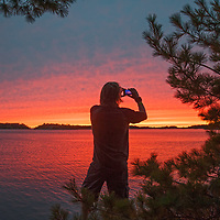 A camper admires a sunset over Lake of the Woods, Ontario, Canada.