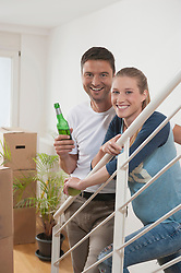 Couple drinking beer in new home, Bavaria, Germany