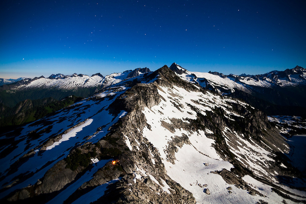 A campfire glows at night below Hidden Lake Peaks, North Cascades National Park, Washington.