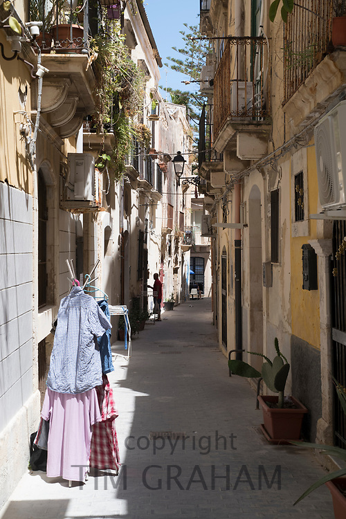 Balconies, lanterns and laundry in street scene in alleyway in Greek Streets by via Della Giudecca, Ortigia, Syracuse, Sicily