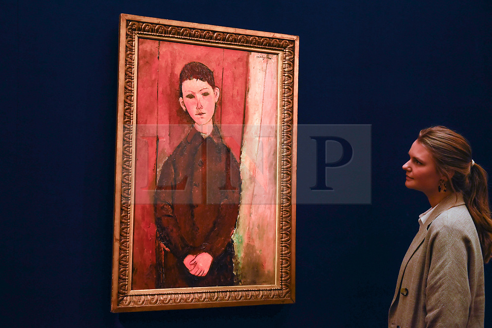 """© Licensed to London News Pictures. 14/06/2019. LONDON, UK. A staff member views """"Jeune Homme Assis, Les Mains Croisées sure les Genoux"""", 1918, by Amedeo Modigliani (Est. £16-24m). Preview of Impressionist and Modern art sales, which will take place at Sotheby's New Bond Street on 18 and 19 June 2019. Photo credit: Stephen Chung/LNP"""
