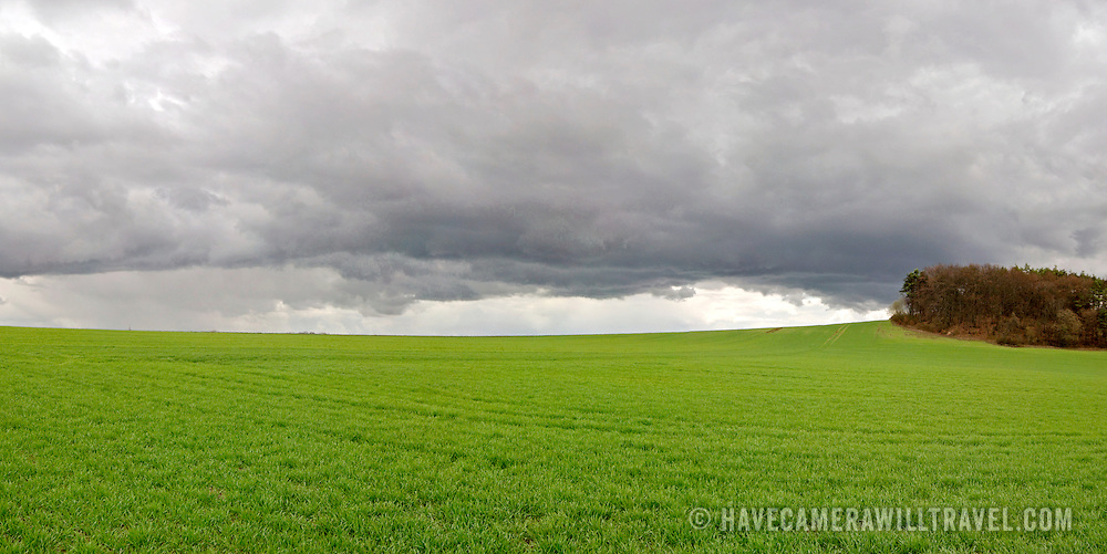 Storm clouds over a green meadow in Cote de Nuits, near Beaune, Bourgogne, France.