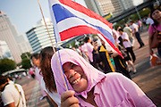 """Apr. 2, 2010 - BANGKOK, THAILAND: A Pink Shirt uses a pink towel to shield her from the sun at a peace rally in Bangkok Friday. Thousands of """"Pink Shirts,"""" who claim to be neither """"Red Shirts"""" nor """"Yellow Shirts"""" nicknames for Thailand's dueling political forces, gathered in Lumpini Park in central Bangkok Friday evening to call for """"peace in the land,"""" a play on the Red Shirts slogan, """"Red in the Land."""" The """"Pink Shirts"""" represented educators, business people and people in the tourist industry, all of which have been hurt by the ongoing political protests that have disrupted life in the Thai capital. The """"Pink Shirts"""" stressed their loyalty to His Majesty Bhumibol Adulyadej, the King of Thailand, and chanted for the Red Shirts to """"Get Out!"""" of Bangkok.    PHOTO BY JACK KURTZ"""