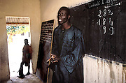 A young boy with elephantiasis looks in on his school classroom during a math class. Kouakourou, Mali. (Supporting image from the project Hungry Planet: What the World Eats.)