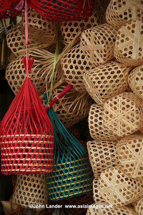 Baskets at Chatuchak Market or sometimes written Jatujak or Weekend Market in Bangkok is the largest market in Thailand, and one of the largest of the world.  Frequently called J.J. it covers over 35 acres and contains more than 5,000 stalls not counting wandering vendors and street entertainers. It is estimated that the market receives between 200,000 and 300,000 visitors each day. Most stalls are only open on Saturdays and Sundays. The market offers a wide variety of products including household items, clothing, Thai handicrafts, religious artifacts, collectibles, foods, and even live animals.
