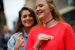 © Licensed to London News Pictures. 18/09/2014. Glasgow, UK. Two teenage girls putting 'No' stickers on in Glasgow city centre whilst people of Scotland going to polling stations to vote on the Scottish independence referendum on Thursday, 18 September 2014. Photo credit : Tolga Akmen/LNP