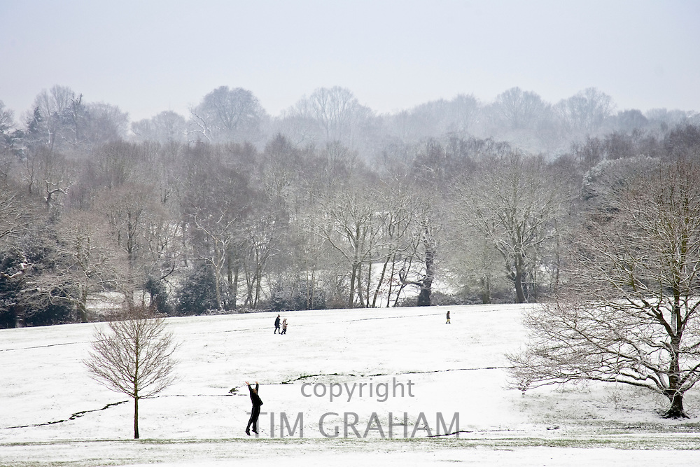 Man exercises in snow-covered Hampstead Heath, North London, England, United Kingdom