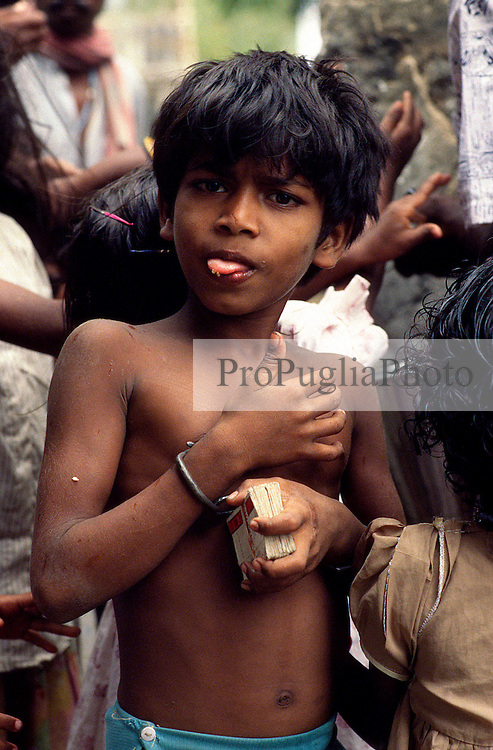 TAMIL NADU, MARCH 1994.A child who wears hand cuffs poks his tongue out and looks inquisitive at the camera. .This is the fate awaiting those who the locals believe are possessed by evil spirits..