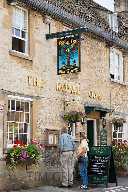 Tourist couple view food menu at The Royal Oak inn traditional old gastro pub hotel in Burford, The Cotswolds, Oxfordshire, UK