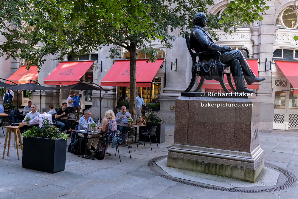 In the week that many more Londoners returned to their office workplaces after the Covid pandemic, after-hours drinkers enjoy the shade next to the statue of George Peabody during late summer temperatures in the City of London, the capital's financial district, on 8th September 2021, in London, England. George Peabody (1795 to 1869) was a philanthropist, banker and entrepreneur.