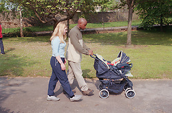 Young mother and father walking through park pushing baby in pram,