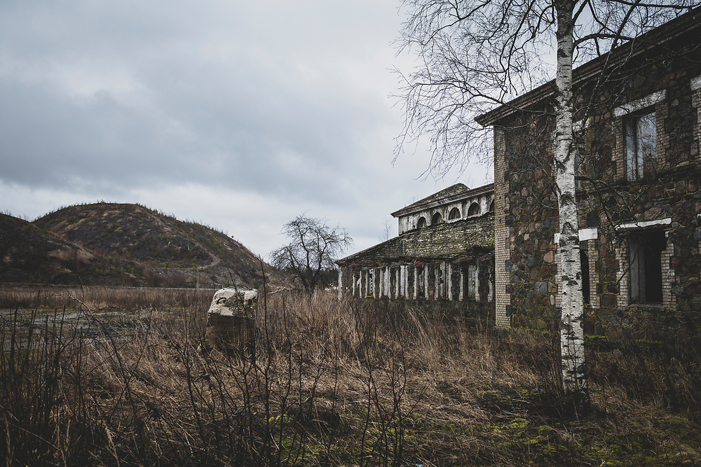 Sompa, Estonia - February 22, 2020: Built in the late 1940s by German prisoners of war and now in disrepair, this building was part of the shale oil mining operation in Sampa from 1948-1999. On the left are hills made of oil shale ash.