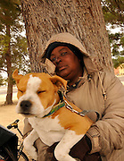 A homeless woman and her dog, along with others living on the streets, spend the day in Anza Park after spending the night in a Salvation Army shelter in Tucson, Arizona, USA.