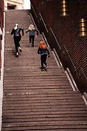 Three girls running up the stairs