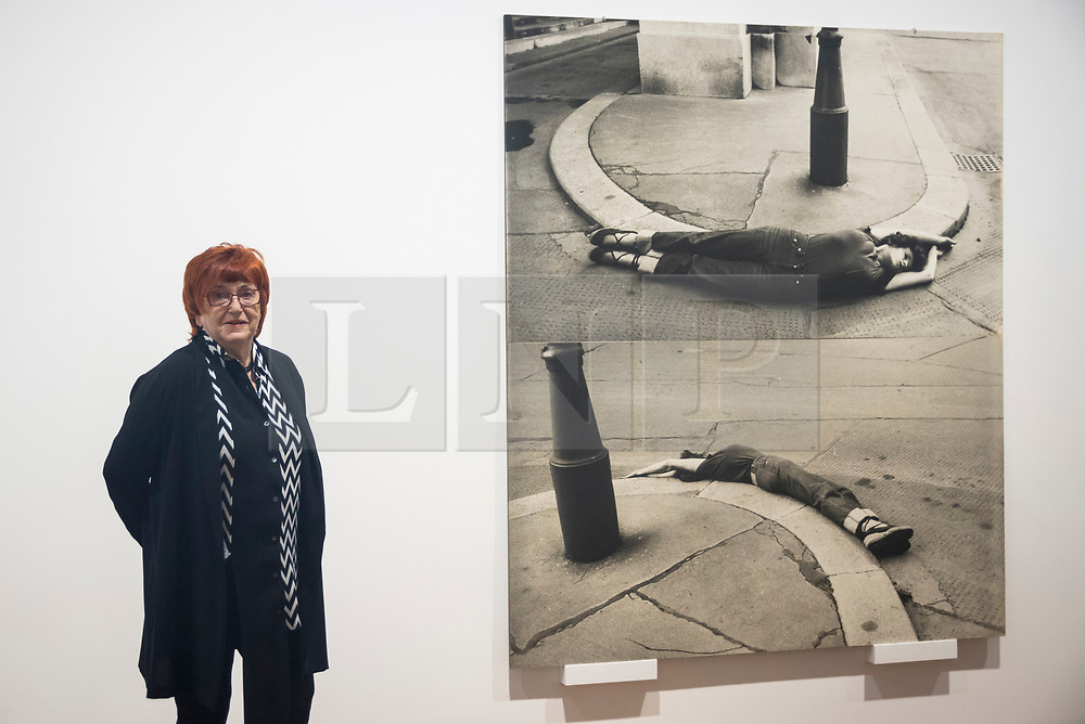 """© Licensed to London News Pictures. 28/11/2019. LONDON, UK. Austrian artist Valie Export poses with works from her """"Arbrundung"""", 1976, series at the preview of her exhibition """"The 1980 Venice Biennale Works"""" at Galerie Thaddeus Ropac in Mayfair.  The exhibition comprises innovative multimedia installation from the 39th Venice Biennale and 17 large-scale photographs mounted on wooden panels from her important photographic series Body Configurations (1972–82).  The show runs 28 November to 25 January 2020.  Photo credit: Stephen Chung/LNP"""