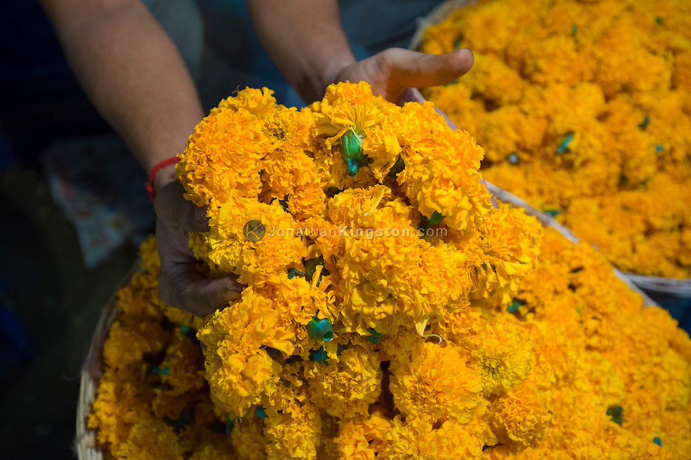 A man holds a handful of marigold flowers at a market in India.