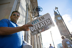 © licensed to London News Pictures. London, UK 30/08/2013. A newspaper distributor handing out City AM newspapers, which show MPs decision against possible military action against Syria, outside Houses of Parliament in London. Photo credit: Tolga Akmen/LNP
