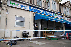 © Licensed to London News Pictures. 27/04/2020. London, UK. A police officer guards a crime scene outside an address on Aldborough Road North in Ilford where ,last night, two children were stabbed to death and a 40 year old man suffered knife injuries  . Photo credit: George Cracknell Wright/LNP