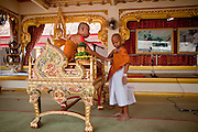 06 APRIL 2010 - THAT PHANOM, THAILAND: The abbot shows a young novice how to put on his saffron monk's robes during an ordination ceremony for novice monks at Wat That Phanom in That Phanom, Thailand. The temple is one of the most sacred in Thailand, local legend says the Buddha's breast bone is in the temple. The temple was originally built in the 6th century AD and assumed its current form in the 15th century when the area was ruled by Lao Kings. The centerpiece of the temple is a 57 meter tall That, or Lao style chedi which is covered with 110 kilos of gold.    PHOTO BY JACK KURTZ
