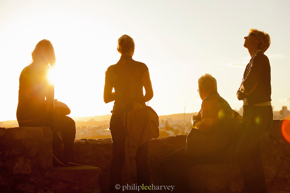 People gather to watch the sunset over Lisbon from the Castle of Sao Jorge, Portugal