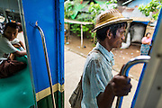 15 JUNE 2013 - YANGON, MYANMAR:  A man gets ready to get off the Yangon Circular Train as it pulls into his stop. The Yangon Circular Railway is the local commuter rail network that serves the Yangon metropolitan area. Operated by Myanmar Railways, the 45.9-kilometre (28.5mi) 39-station loop system connects satellite towns and suburban areas to the city. The railway has about 200 coaches, runs 20 times and sells 100,000 to 150,000 tickets daily. The loop, which takes about three hours to complete, is a popular for tourists to see a cross section of life in Yangon. The trains from 3:45 am to 10:15 pm daily. The cost of a ticket for a distance of 15 miles is ten kyats (~nine US cents), and that for over 15 miles is twenty kyats (~18 US cents). Foreigners pay 1 USD (Kyat not accepted), regardless of the length of the journey.     PHOTO BY JACK KURTZ