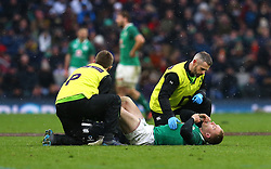Ireland's Keith Earls receives treatment after picking up an injury during the NatWest 6 Nations match at Twickenham Stadium, London.