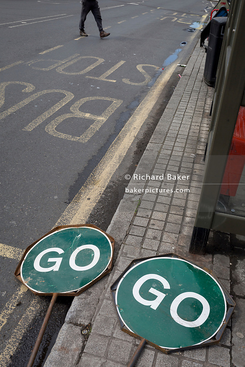 A pedetrian walks past two GO traffic road signs lying on the ground in East Dulwich, on 26th April 2018, in London, England.